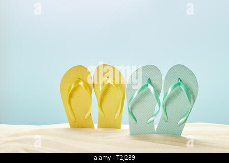 Estate giallo e blu flip flop in sabbia isolata su blu Foto Stock