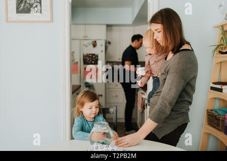 Toddler femmina a tavola con la madre e il bambino fratello Foto Stock