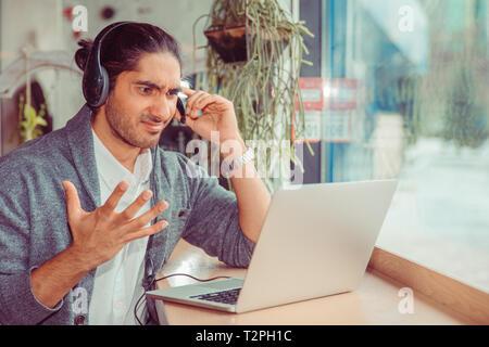 Call center un dipendente che lavora in ufficio cercando frustrati per laptop. Closeup ritratto di un bagno turco bello ragazzo indossa formale camicia bianca e grigia bl Foto Stock