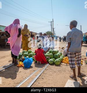 Nuri, Sudan, Febbraio 9, 2019: mercato stallo in Sudan con i cocomeri, con una donna in un mantello blu, una donna con pantaloni, una piccola ragazza giovane con Foto Stock