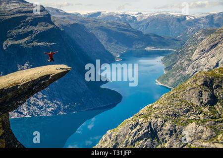 Un Uomo in camicia rossa di saltare sul Trolltunga rock con un lago blu 700 metri più in basso e interessante cielo di nuvole. Foto Stock
