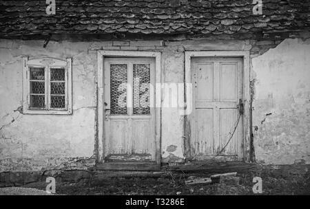 Porte e finestra di un vecchio abbandonato casa del villaggio di Cigoc nella contea di Sisak-Moslavina in Croazia Centrale Foto Stock