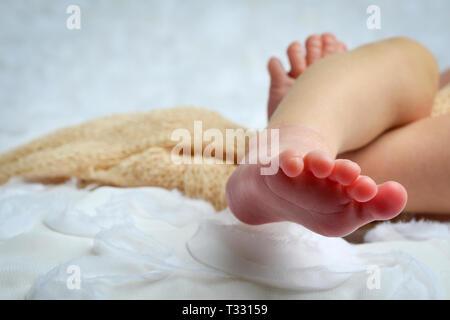 Un ritagliato Close up di un neonato di dita e piedi in bianco e di colore neutro dannoso Foto Stock