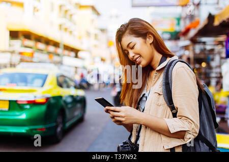 Giovani asiatici turista femminile donna utilizzando un telefono cellulare a Bangkok, in Thailandia. Chiamare un taxi o la ricerca di informazioni durante il concetto di viaggio