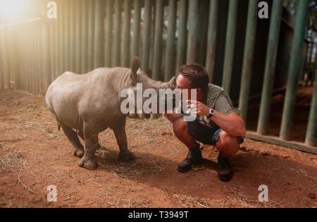 Giovane uomo kissing rinoceronte baby Foto Stock