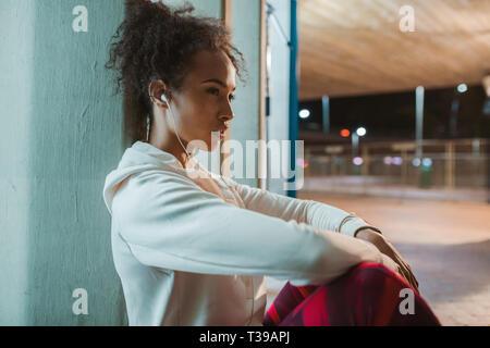 Vista laterale della giovane donna seduta sotto un ponte e prendere il resto dopo l'esecuzione di esercizio fisico. Urban runner riposo dopo la formazione nella notte. Foto Stock