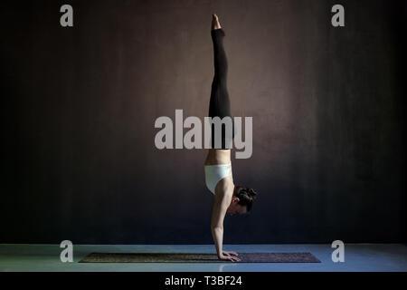 Giovane donna yogi la pratica dello yoga, in piedi Adho Mukha Vrksasana esercizio, rivolte verso il basso la posizione dell'albero. Lunghezza completa studio shot Foto Stock
