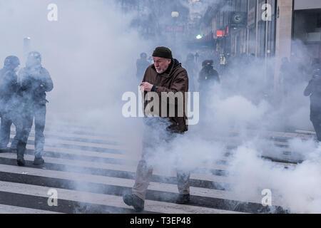 Un vecchio uomo passeggiando per strappare gaz durante un 'giallo' giubbotti di dimostrazione sulla piazza della Repubblica a Parigi il 2 febbraio 2019 Foto Stock