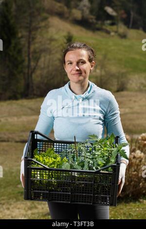 Donna giardiniere mostra piantine collezione preparato per essere piantato in giardino. Giardinaggio organico, sana e cibi caserecci, auto-approvvigionamento concetto. Foto Stock