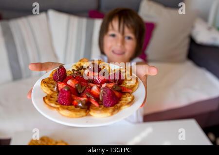 Dolce ragazzo di compleanno, mangiare i waffle belgi con fragole e lamponi e il cioccolato a casa