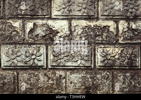 Muro di pietra con fiore rilievo su ciascun mattone in pietra, vecchio e stagionato Foto Stock