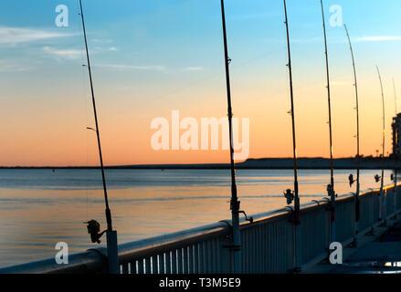Poli di pesca rimangono inattivi come il sole tramonta a Florida punto pier, nov. 12, 2009, in Orange Beach, Alabama.