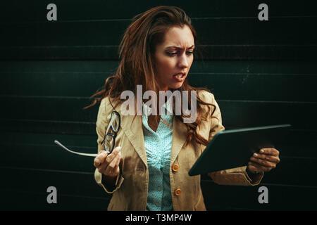 Giovane e bella donna worriedly holding tavoletta digitale nelle sue mani e analizzando il nuovo progetto nel distretto di office.