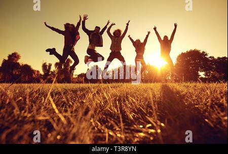 Un gruppo di giovani persone che saltano sull'erba nel parco al tramonto. Foto Stock