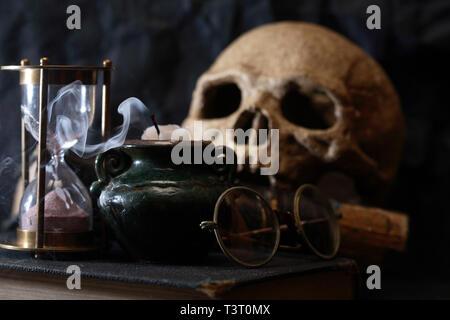 Scienza antica nozione. Cranio umano sul vecchio libro vicino a clessidra e candela Foto Stock