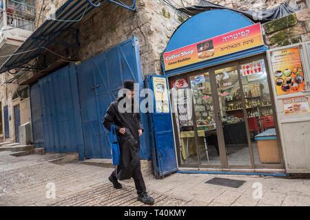 Un ebreo ortodosso uomo cammina davanti a un ristorante palestinese nella città vecchia di Gerusalemme, Israele, 15/03/19