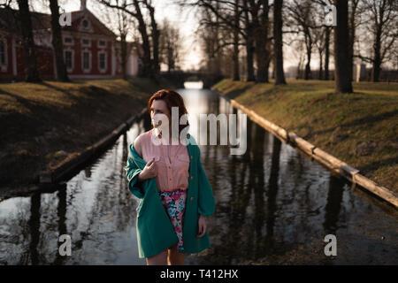 Bella giovane donna rilassante vicino a un fiume di canale in un parco vicino al Palazzo di Rundale, Lettonia, 2019
