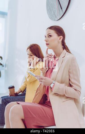 Messa a fuoco selettiva di pensieroso donna utilizza lo smartphone vicino dipendente con bicchiere di carta Foto Stock
