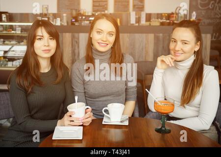 Tre donne fidanzate in un cafè sono a parlare e a bere la loro bevande, la luce del sole Foto Stock