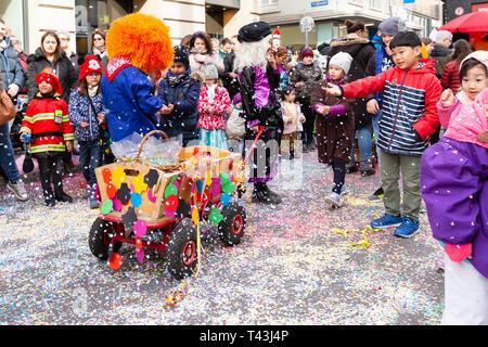 Freie Strasse, Basilea, Svizzera - Marzo 12th, 2019. Un piccolo colorato carnevale decorata carrello su una coperta di confetti street Foto Stock