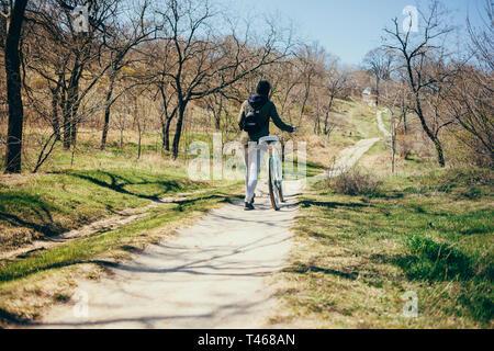 Escursioni in bicicletta nella natura. Vista posteriore del giovane donna cammina accanto alla sua bici in salita nel bosco sulla soleggiata giornata di primavera.