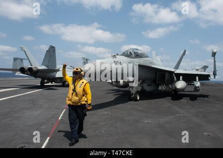Stati Uniti Aviazione Navale di Boatswain Mate (manipolazione) 1a classe Forrest Findley, da Sammamish, Washington, dirige un EA-18G Growler assegnata all attacco elettronico Squadron (VAQ) 133, per rimanere in posizione sul ponte di volo della portaerei USS John C. Stennis CVN (74) nell'Oceano Indiano, 15 marzo 2019. John C. Stennis Carrier Strike gruppo è distribuito negli Stati Uniti Quinta Flotta area di operazioni a sostegno di operazioni navali per garantire stabilità marittimo e la sicurezza nella regione centrale di collegamento del Mediterraneo e del Pacifico attraverso l'Oceano Indiano occidentale e tre strategici chok