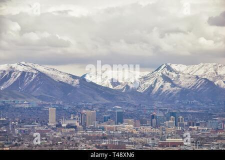Centro cittadino di Salt Lake City vista panoramica di Wasatch Front Montagne Rocciose da aereo a inizio primavera inverno con fusione della neve e cloudscape. Utah, U Foto Stock