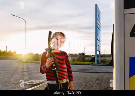Bambino tenere il tubo di una pompa del carburante al tramonto in corrispondenza di una stazione di gas. Foto Stock