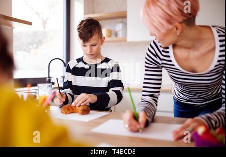 Una giovane donna con due bambini disegno in una cucina.