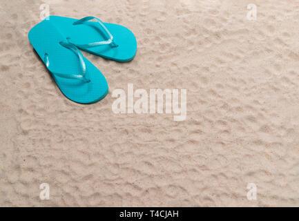 Inquadratura orizzontale di una spiaggia di sabbia con uno sfondo con una coppia di blu flip-flop nell'angolo superiore sinistro. Copia dello spazio. Foto Stock