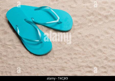 Inquadratura orizzontale di una coppia Blue Flip Flop nell'angolo in alto a sinistra sulla spiaggia di sabbia con copia spazio. Foto Stock