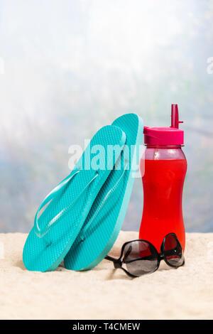 Colpo verticale di una bevanda di colore rosso con una coppia di blu flip-flop di appoggiarsi su di essa e un paio di occhiali da sole neri tra di loro. Tutti su una vacanza di sabbia beac Foto Stock