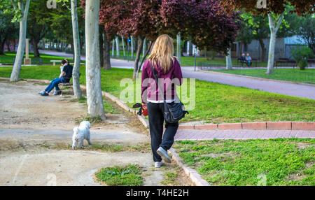 Donna bionda prende il suo cane per una passeggiata con un guinzaglio in un percorso al parco. Le donne a piedi cane a parchi in Murcia, Spagna, 2019