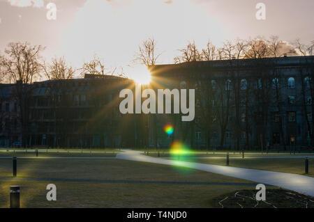 Sun dietro di sagome di alcuni edifici e di un bel verde scuro park Foto Stock