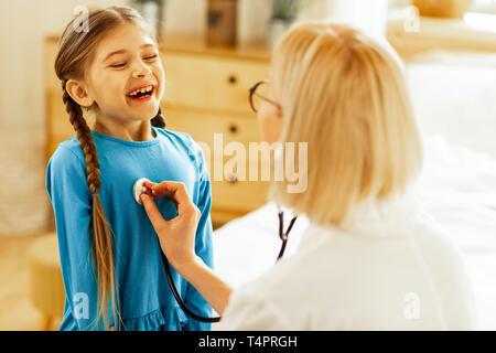 Per respirare. Un simpatico bella piacevole con i capelli lunghi ragazza prendendo un respiro profondo mentre un biondo pediatra attraente in bicchieri controllando i suoi polmoni. Foto Stock