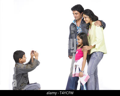 Un giovane ragazzo prende una fotografia della sua famiglia Foto Stock