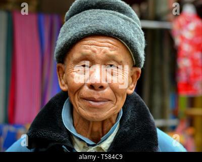 Il vecchio cinese Han uomo indossa un cappello di lana e pone per le telecamere. Foto Stock