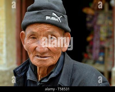Il vecchio cinese Han mano fattoria con vissuto in faccia indossa un capo di lana zucchetto e pone per la fotocamera. Foto Stock