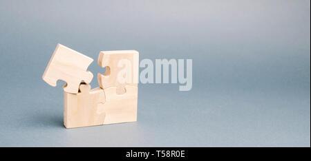 Puzzle in legno su sfondo grigio. Un puzzle è diverso. Parere individuale. Distinguiti dalla folla. Unicità. Le divergenze di opinioni. Con differenti Foto Stock