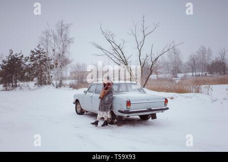 La donna si trova nei pressi dell' automobile in inverno in natura Foto Stock