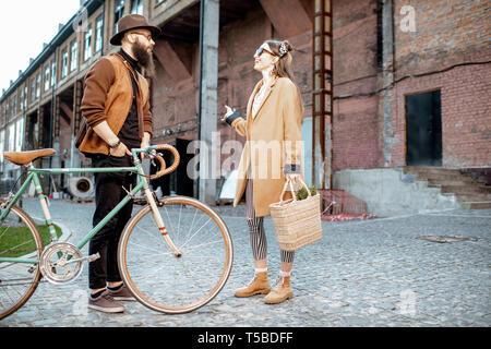Elegante giovane uomo e donna avente una conversazione in piedi insieme con bicicletta retrò all'aperto su industriale di background urbano