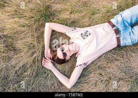 Giovane donna sull'erba prendendo il tempo di apprezzare la molla. Vista dall'alto di un sorridente persona di sesso femminile che stabilisce nel prato o un campo guardando il cielo