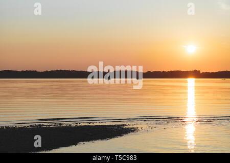 Un tramonto meraviglioso nel lago Chiemsee con barca a vela navigazione Foto Stock