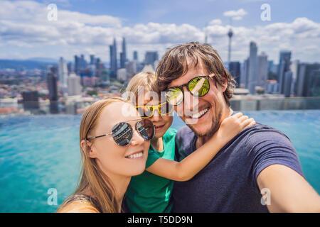 Vacanze e tecnologia. La famiglia felice con kid tenendo selfie insieme vicino alla piscina con viste panoramiche della città