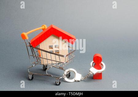Una persona è ammanettato ad una casa su di un carrello per supermercati. Il concetto di un enorme debito su di un prestito o di un credito ipotecario. Dipendenza finanziaria, alloggiamento non disponibile Foto Stock