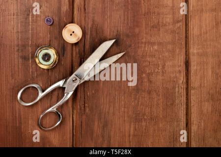 Vintage forbici e pulsanti, ripresa dall'alto su una scuri in legno rustico sfondo con un posto per il testo