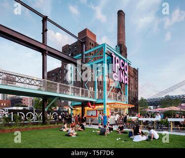Ristorante Tacocina contro lo sfondo del Domino ex fabbrica di zucchero. Domino Park, Brooklyn, Stati Uniti. Architetto: James angolo opera sul campo Foto Stock