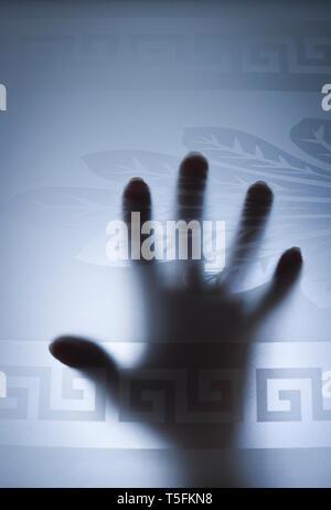 Messa a fuoco selettiva - mani silhouette dietro un vetro smerigliato porta. Il concetto di paura, grido di aiuto, pericolo. Foto Stock