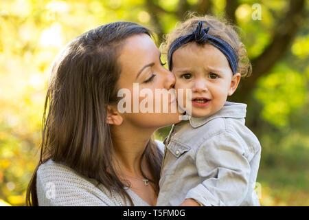 Madre baciare bambina all'aperto in autunno Foto Stock
