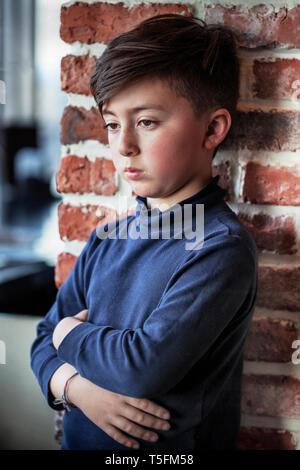 Razza mista Asian Caucasian boy con le braccia incrociate indossando blue turtleneck shirt nella parte anteriore del rosso parete di mattoni
